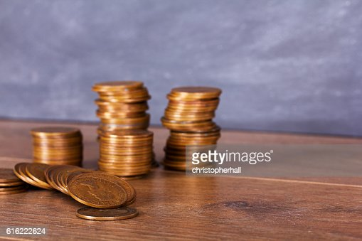 Stack of penny coins on a wooden surface : Stock Photo