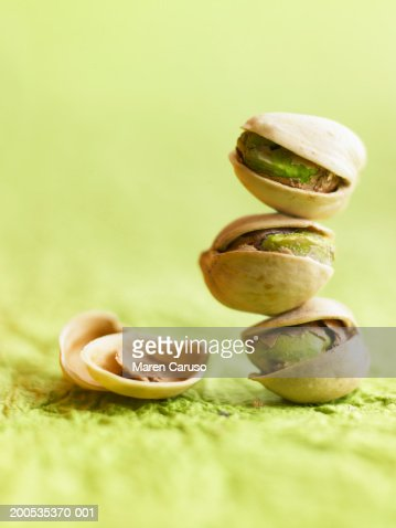 Stack of pistachios beside nutshell