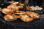 Stack of pitas at barbecue outdoors. Middle eastern home made freshly baked on large bbq with sausages