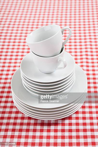A stack of plates, saucers and coffee cups