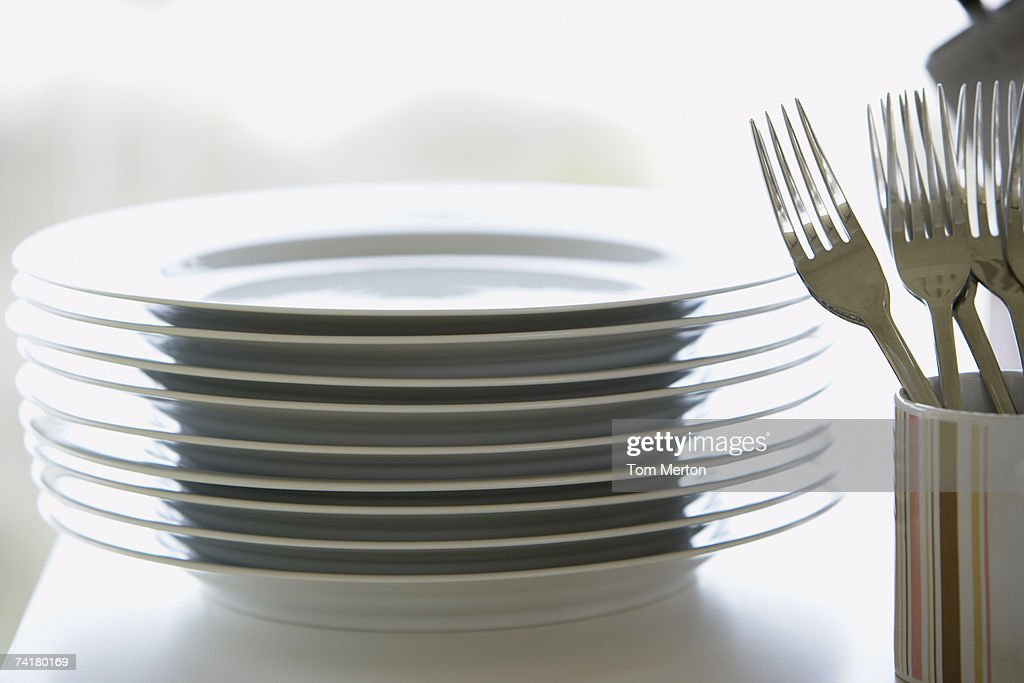 Stack of plates with forks in mug : Stock Photo
