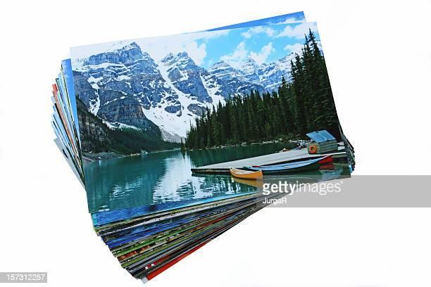 Une pile de photos imprimées vacances sur fond blanc