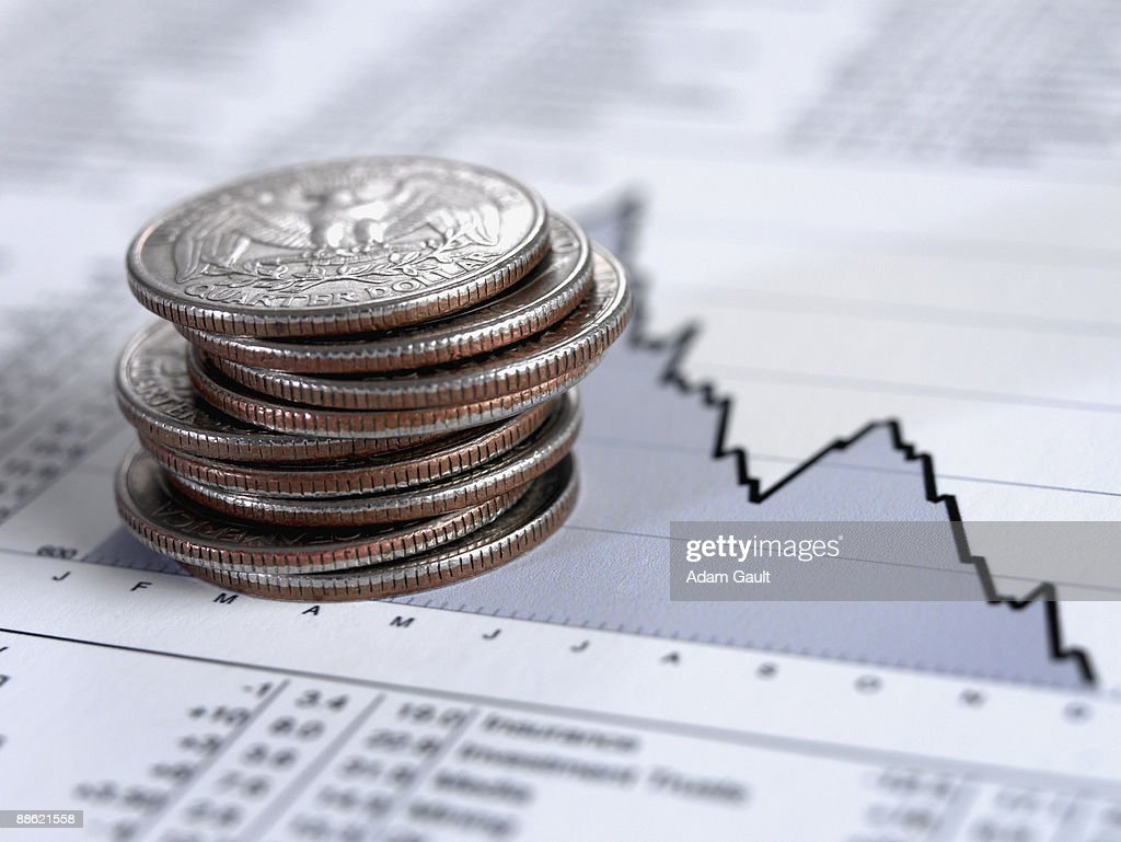 Stack of quarters on descending line graph : Stock Photo