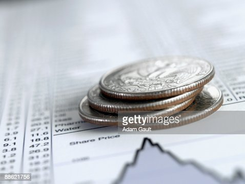 Stack of quarters on list of share prices : Stock Photo