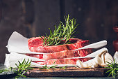 Stack of  raw steaks with rosemary at dark wooden background, side view