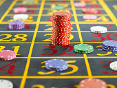 Stack of red gambling chips over two numbers on roulette table