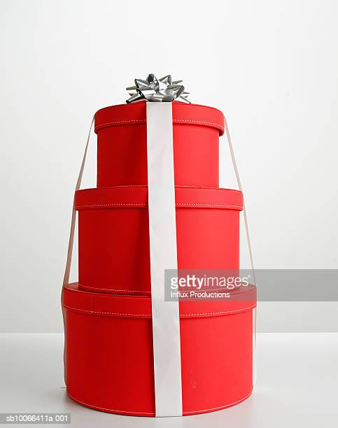 Stack of red round gift boxes with silver bow