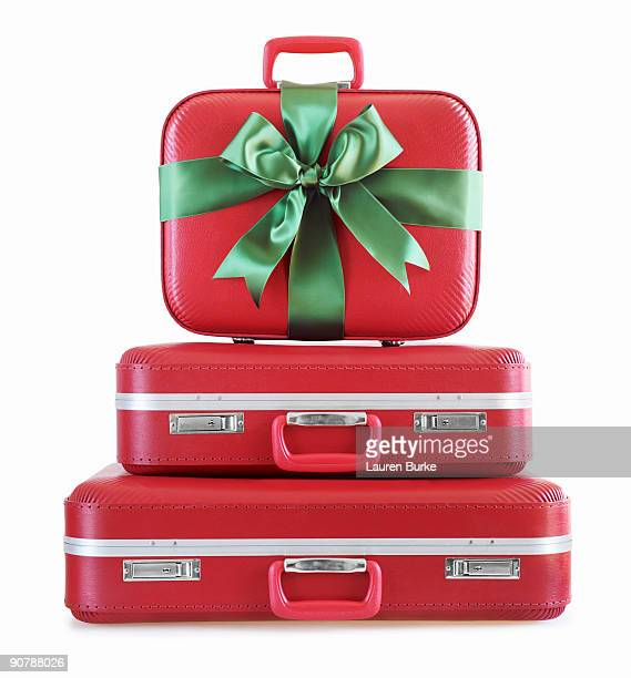 Stack of Red Suitcases Wrapped in Green Ribbon