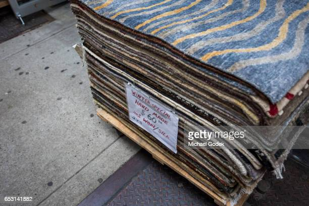 A stack of rugs for sale sit on a palate outside a storefront in Manhattan