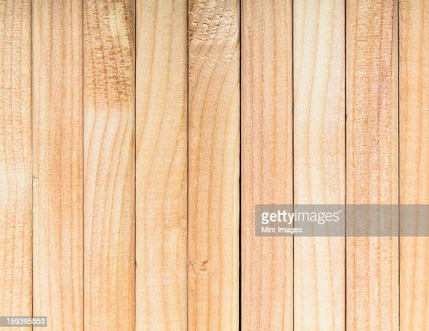 Stack of sawn prepared timber, spruce wood planks or studs, for use. Treated planed wood in traditional 2 by 4 measured cut shapes.