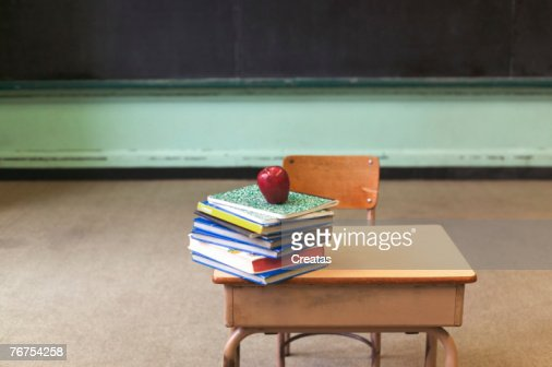 Stack of school books and apple on desk in empty classroom : Stock Photo