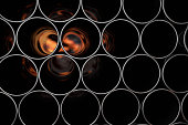 Stack of metal pipes, flame, tubes with reflections.