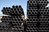 stack of industrial steel tubes against clear blue sky