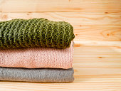Stack of sweaters on wooden background with copy space. Winter clothing concept.