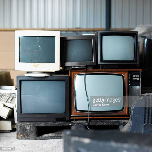 stack of televisions and computer monitors