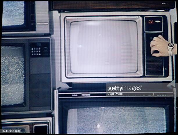 Stack of televisions, hand turning TV dial (video still)