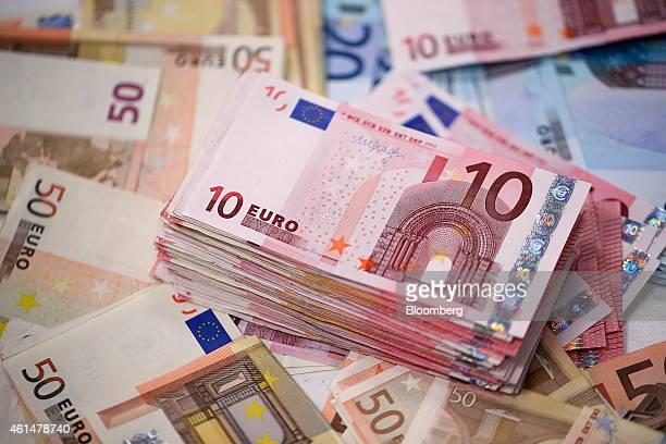 A stack of ten euro banknotes is arranged with fifty and twenty euro banknotes for a photograph inside a Travelex store operated by Travelex Holdings...