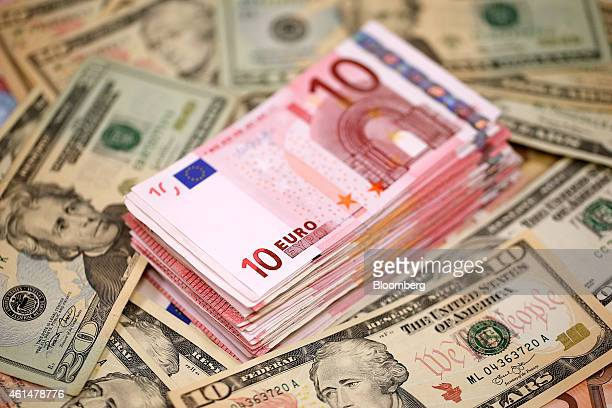 A stack of ten euro banknotes sit on a pile of US dollar bills in this arranged taken photograph inside a Travelex store operated by Travelex...