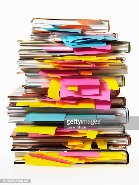 Stack of textbooks with post-it notes in pages, studio shot