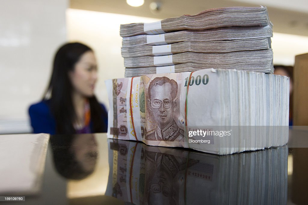 A stack of Thai 1000 Baht banknotes sit on a counter at the Bangkok Bank Pcl. headquarters in Bangkok, Thailand, on Tuesday, Jan. 8, 2013. Thailand's economy may have expanded 5.7 percent in 2012 and will grow 5 percent in 2013, the finance ministry said on Dec. 26. Photographer: Brent Lewin/Bloomberg via Getty Images