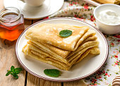 Stack of thin pancakes crepes bliny served with honey and sour cream