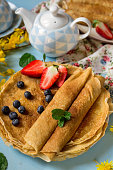 Stack of thin pancakes crepes with fresh strawberries and blueberries