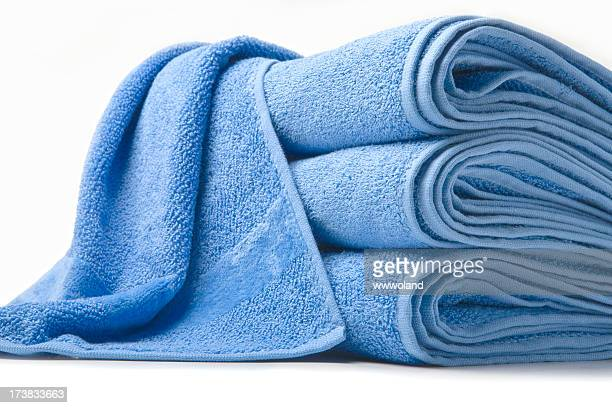 Stack of three blue towels and one thrown on top