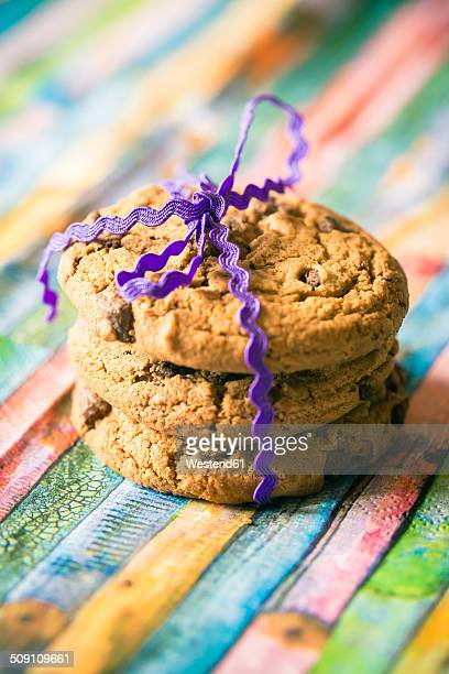 Stack of three chocolate cookies on coloured wood