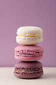 Stack of three pink macarons cookies on tile