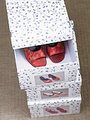 Stack of three shoe boxes with pair of ladies patterned toeless shoes in top box