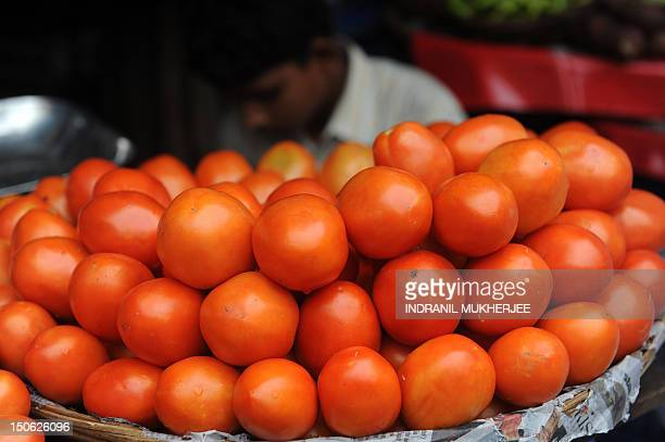 A stack of tomatoes are seen on display at a street side market in Mumbai on June 14 2010 Indian inflation broke into double figures in May hitting...