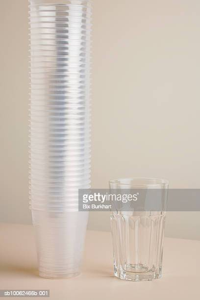 Stack of transparent disposable cups beside drinking glass on table