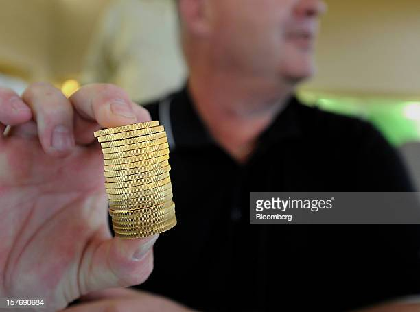 A stack of twenty one once ounce gold coins is displayed for a photograph during an auction of the contents of the corporate offices of Peregrine...
