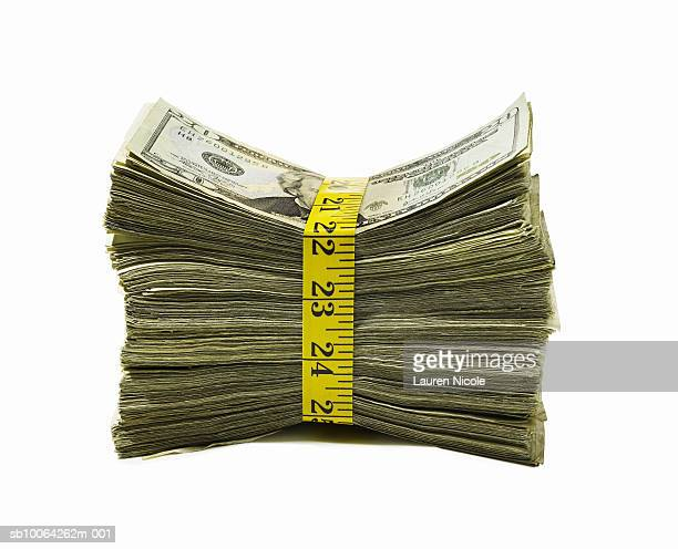 Stack of US currency wrapped in measuring tape