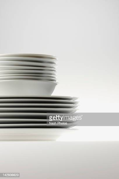 Stack of white bowls on a stack of white plates