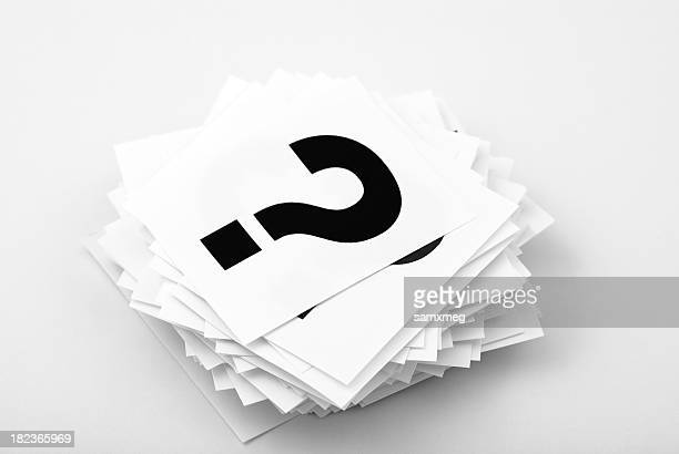 A stack of white cards with black question marks