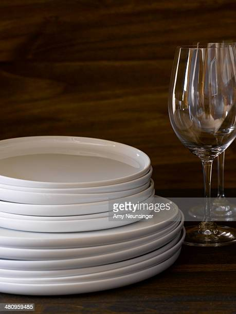 Stack of white plates with wine glasses.