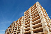 stack of wooden pallets against clear blue sky, low angle view