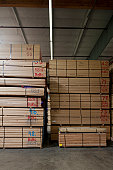 Stack of wooden plywood with markings in warehouse