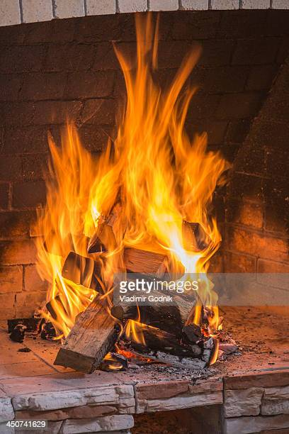 A stack on fire wood ablaze in an open fire