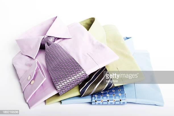 Stack pile of men's blue shirts and ties folded