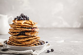 Stack vegan blueberry pancakes with peanut butter and syrup. Clean eating concept.