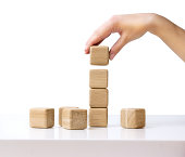Stack of wooden blocks on white table isolated business concept.Hand establishes cube in a raw.Financial growth success.Building tower process.