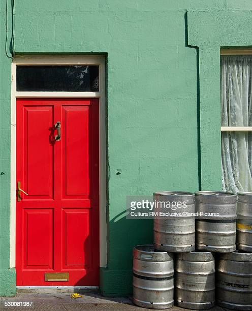 Stacked beer kegs outside house with red door, Ireland