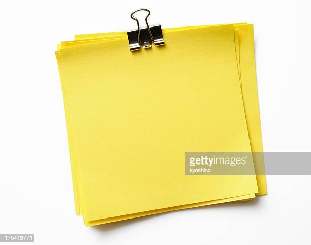 Stacked blank yellow sticky note with paper clip on white