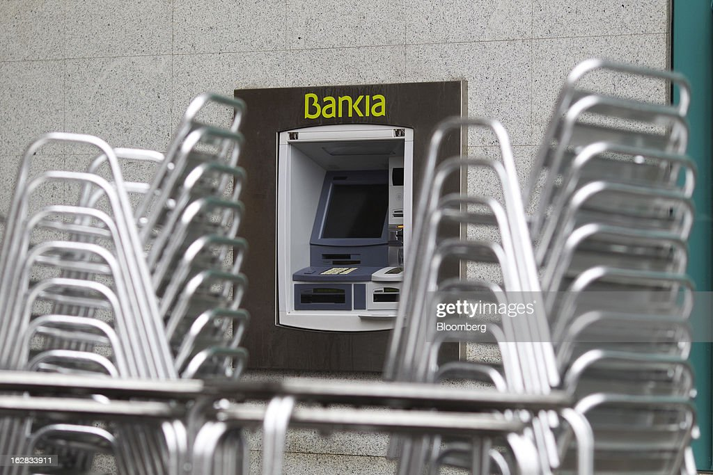 Stacked cafe chairs and tables stand outside an automated teller machine (ATM) in Madrid, Spain, on Thursday, Feb. 28, 2013. BFA-Bankia Chairman Jose Ignacio Goirigolzarri said a balance sheet clean-up that inflicted a 21.2 billion-euro ($27.6 billion) after-tax loss last year will set the Spanish banking group on course to repay state aid. Photographer: Angel Navarrete/Bloomberg via Getty Images