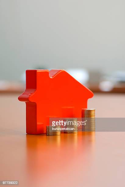 Stacked coins in front of a toy house