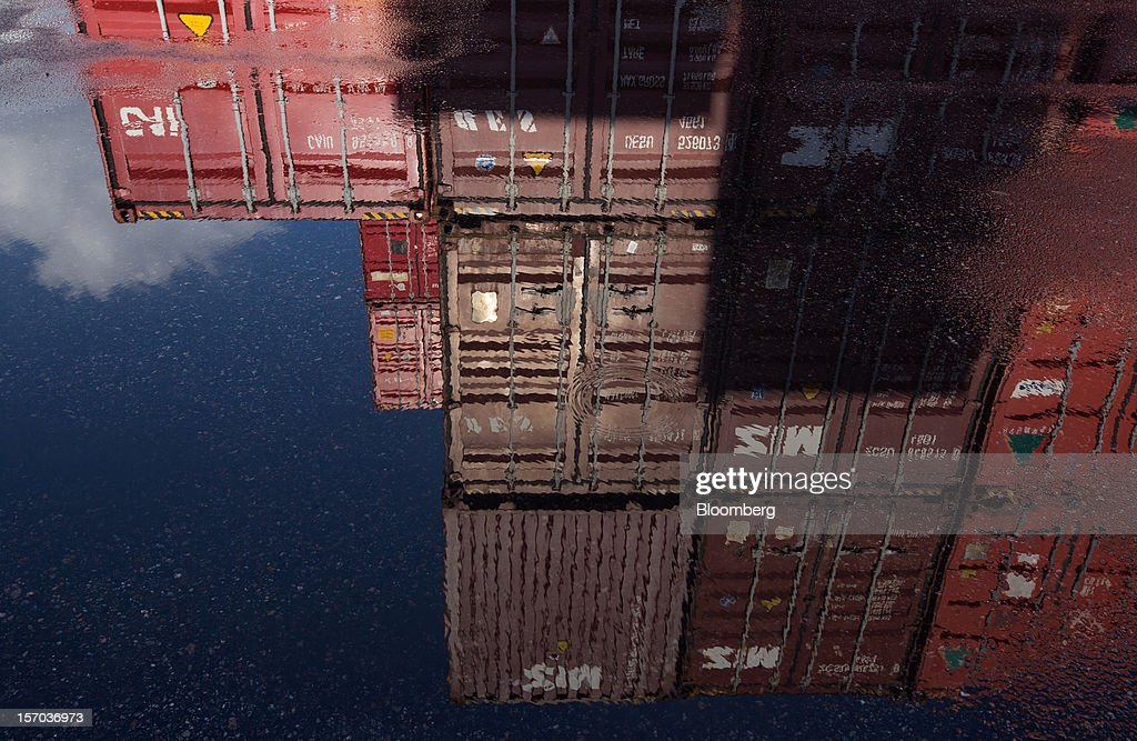 Stacked containers are reflected in a puddle at the Uiwang Inland Container Depot (ICD) in Uiwang, South Korea, on Monday, Nov. 26, 2012. South Korea's current-account surplus narrowed to a two-month low after imports of machinery and equipment increased. Photographer: SeongJoon Cho/Bloomberg via Getty Images