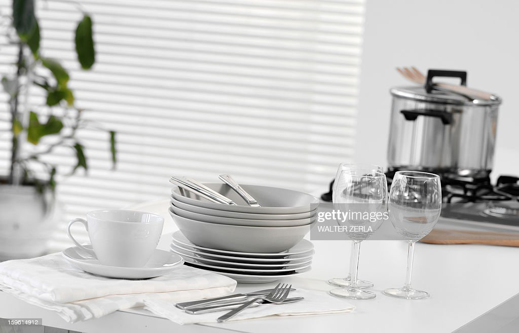 Stacked dishes and cutlery on table : Stock Photo