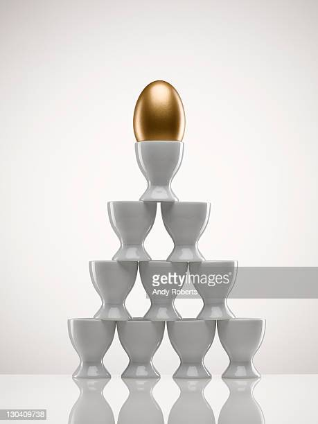 Stacked egg cups with golden egg